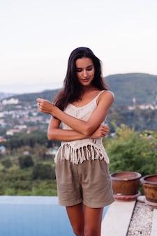 Portret szczęśliwej kaukaskiej spokojnej romantycznej kobiety w swobodnym wyglądzie z długimi włosami noszącymi kolczyki i naszyjnik na tle niesamowitym pięknym widokiem na zielone góry