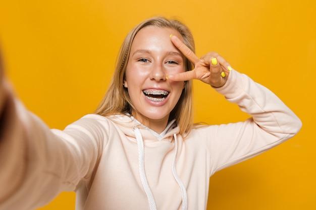 Portret szczęśliwej kobiety 16-18 lat z aparatami ortodontycznymi uśmiecha się i robi selfie, na białym tle na żółtym tle