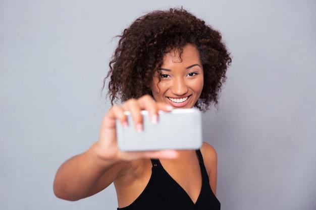 Portret szczęśliwej kobiety afro american co selfie zdjęcie na smartfonie na szarej ścianie