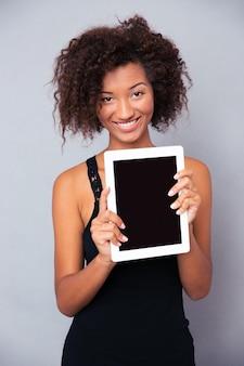 Portret szczęśliwej kobiety afro american pokazano pusty ekran komputera typu tablet na białym tle na białej ścianie