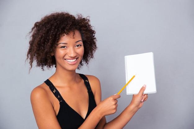 Portret szczęśliwej kobiety afro american pokazano pusty notatnik ołówkiem na szarej ścianie