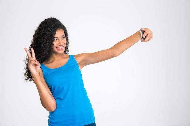 Portret szczęśliwej kobiety afro american robi selfie zdjęcie na białym tle na białej ścianie