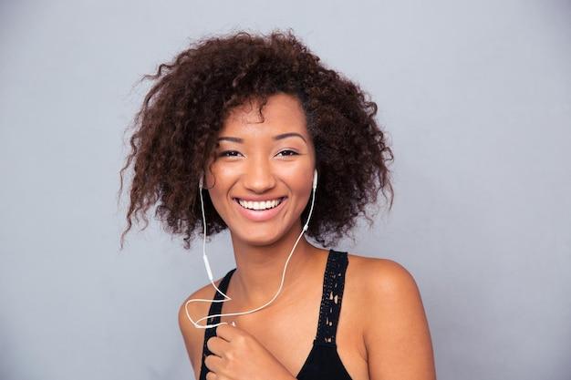 Portret szczęśliwej kobiety afro american słuchanie muzyki w słuchawkach na szarej ścianie