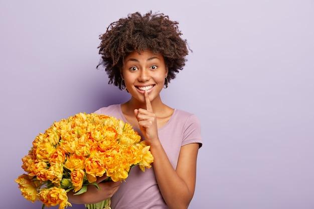 Portret szczęśliwej kobiety afro amerykanki robi gest ciszy z zachwytem, trzyma duży bukiet wiosennych kwiatów