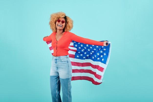 Portret szczęśliwej kobiety afro z amerykańską flagą, stojąc na na białym tle. koncepcja obchodów dnia niepodległości.