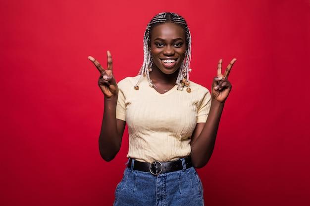 Portret szczęśliwej kobiety afrykańskiej pokazując zwycięstwo palcami na czerwonym tle