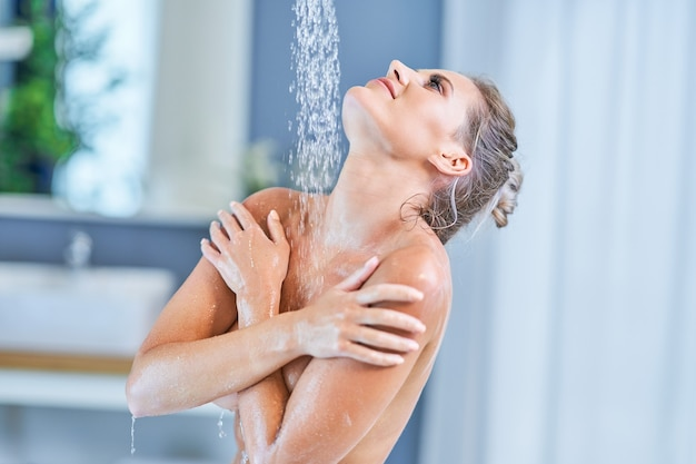 Portret szczęśliwej kobiety biorącej prysznic