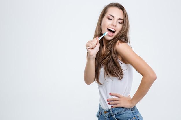 Portret szczęśliwej kobiety czyści zęby szczoteczką do zębów na białym tle