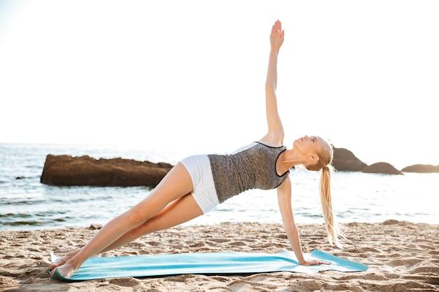 Portret Szczęśliwej Kobiety Fitness Robi ćwiczenia Jogi Na Macie Na świeżym Powietrzu Premium Zdjęcia