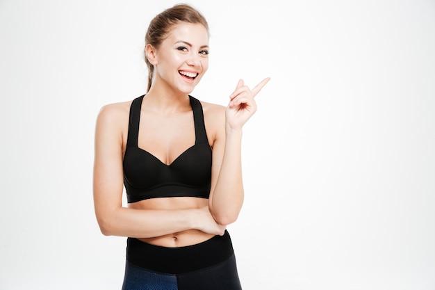 Portret szczęśliwej kobiety fitness wskazujący palec w górę na białym tle