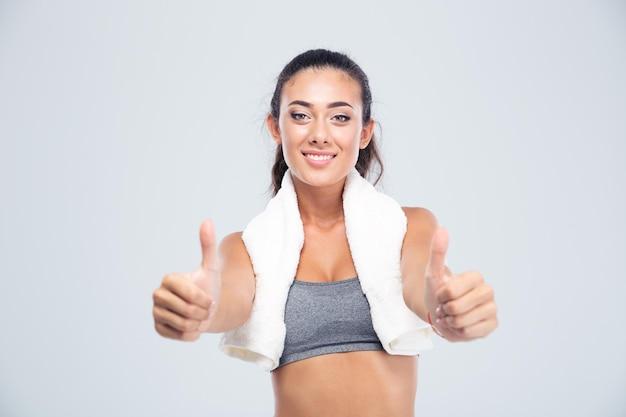 Portret szczęśliwej kobiety fitness z ręcznikiem pokazując kciuki do góry na białym tle na białej ścianie