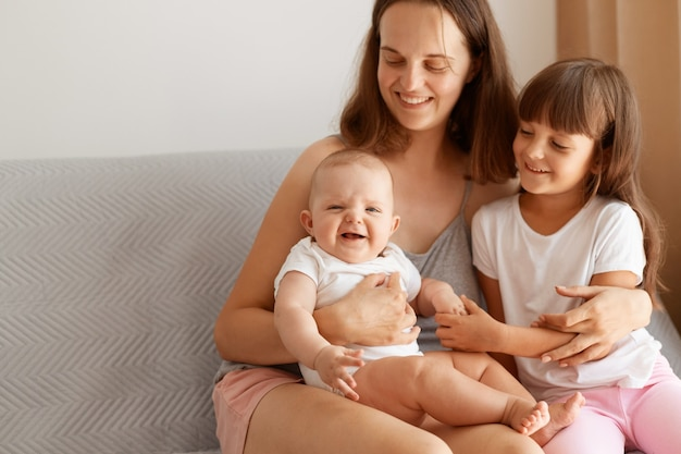 Portret szczęśliwej kobiety matki siedzi na kanapie i przytula swoje urocze urocze córki, uśmiechając się szczęśliwie, wyrażając miłość, troskę i delikatność, pozowanie rodzinne w domu.