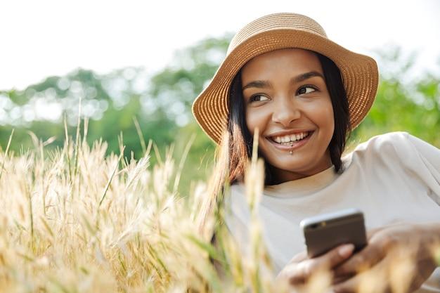Portret szczęśliwej kobiety noszącej przekłuwanie warg i słomkowy kapelusz piszący na telefonie komórkowym, leżąc na trawie w zielonym parku