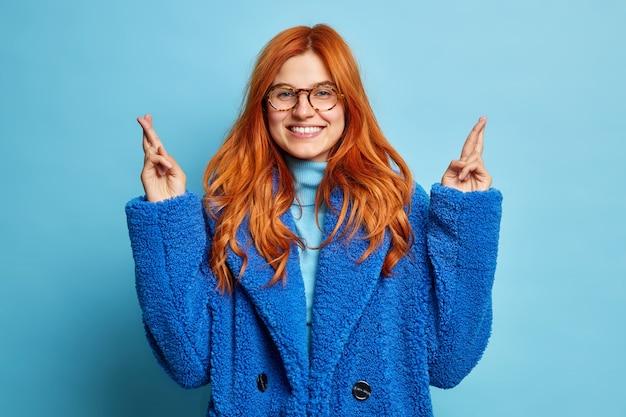 Portret szczęśliwej kobiety o rudych, naturalnych włosach, uśmiecha się przyjemnie, trzyma kciuki ze skrzyżowanymi nadziejami na szczęście ubrana w przezroczyste okulary zimowe futro.