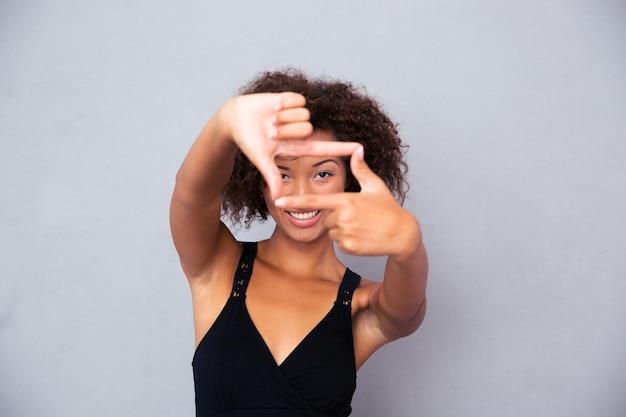 Portret szczęśliwej kobiety patrząc z przodu poprzez gest ramki na białym tle na białej ścianie