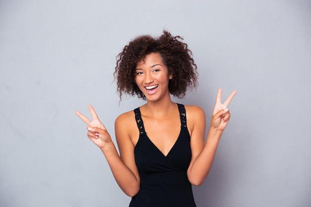 Portret szczęśliwej kobiety pokazując zwycięstwo palcami na szarej ścianie i patrząc z przodu