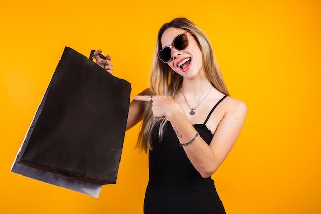 Portret szczęśliwej kobiety pokazującej torby na zakupy na czarnej piątkowej wyprzedaży shopp offers