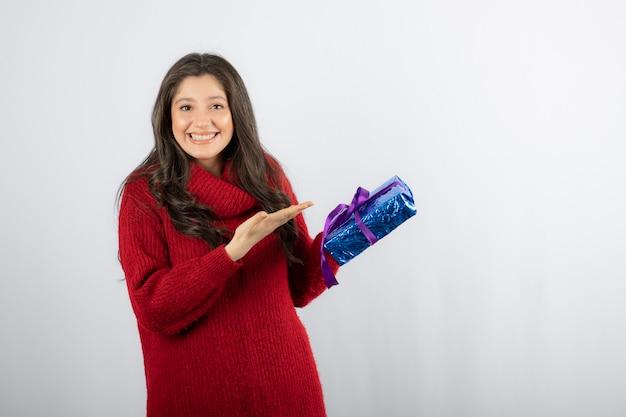 Portret szczęśliwej kobiety pokazujący na boże narodzenie pudełko z fioletową wstążką.