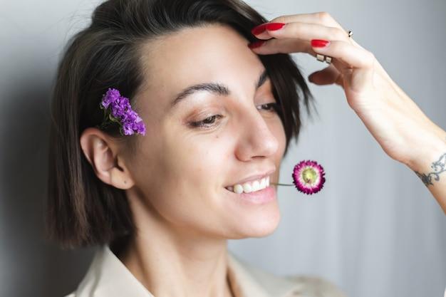 Portret szczęśliwej kobiety rasy kaukaskiej bez makijażu naturalnego piękna trzymając suszony kwiat szary biały.