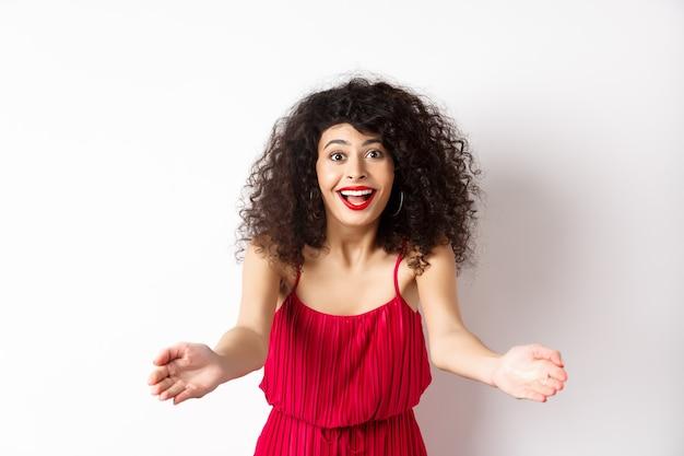 Portret szczęśliwej kobiety rasy kaukaskiej w czerwonej sukience i makijażu, wyciągając ręce, by przywołać kogoś, zapraszając do przytulenia, otrzymując prezent-niespodziankę, stojąc na białym tle.