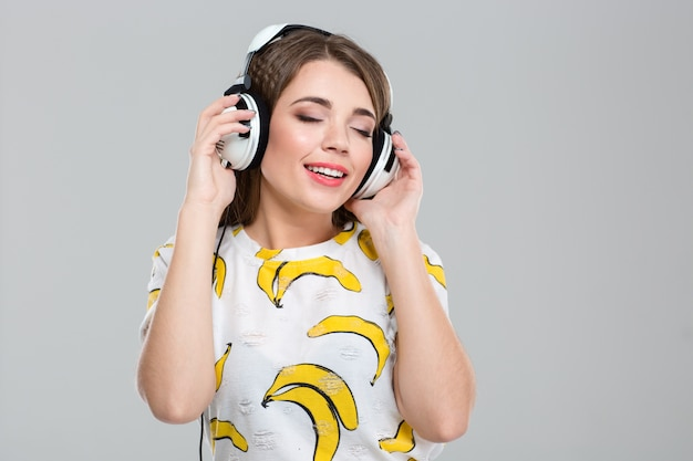Portret szczęśliwej kobiety słuchającej muzyki w słuchawkach na białym tle