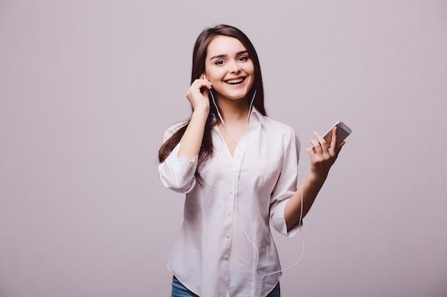 Portret szczęśliwej kobiety słuchania muzyki w słuchawkach na białym tle