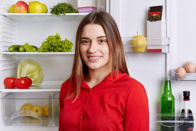 Portret szczęśliwej kobiety stoi w pobliżu lodówki pełnej produktów, szuka jedzenia, robi śniadanie. urocza suczka przy otwartej lodówce, przestrzega diety, je tylko zdrowe jedzenie. koncepcja odżywiania