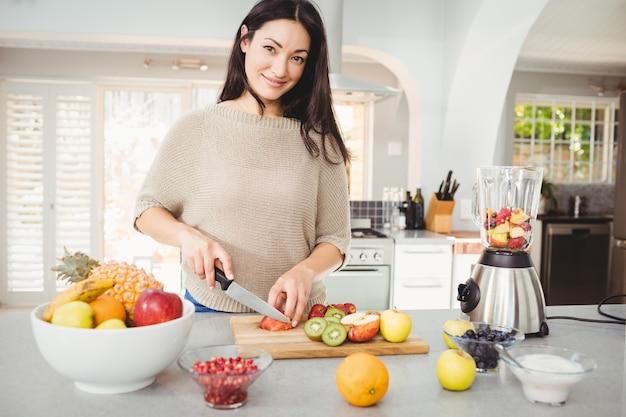 Portret szczęśliwej kobiety tnące owoc