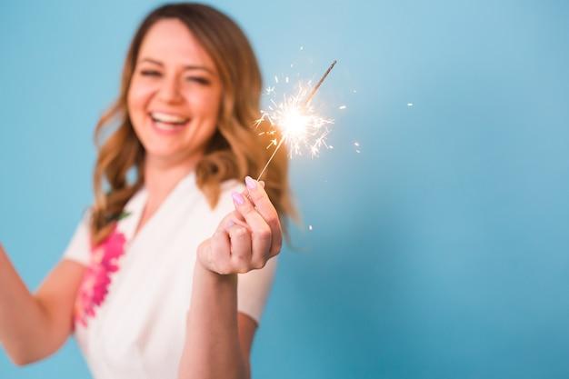 Portret szczęśliwej kobiety trzymającej bengal światła na niebieskim tle z miejsca na kopię. koncepcja bożego narodzenia, uroczystości i świąt