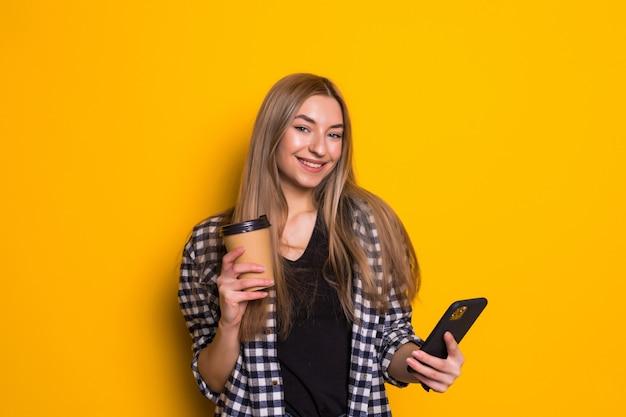 Portret szczęśliwej kobiety trzymającej filiżankę kawy stojąc i używając telefonu komórkowego na żółtej ścianie