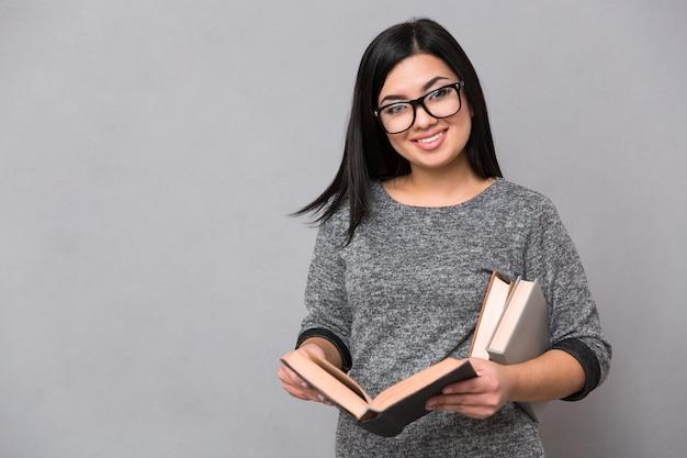 Portret szczęśliwej kobiety trzymającej książki i patrząc z przodu na szarej ścianie