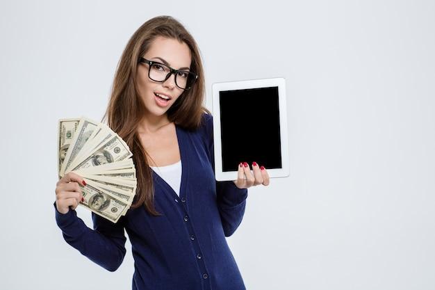 Portret szczęśliwej kobiety trzymającej pieniądze i pokazującej pusty ekran komputera typu tablet na białym tle