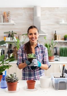 Portret szczęśliwej kobiety trzymającej soczystą roślinę siedzącą na stole w kuchni