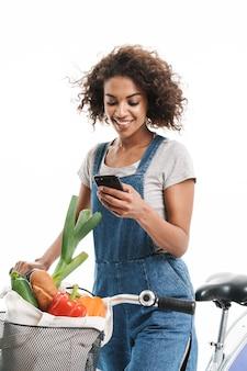 Portret szczęśliwej kobiety trzymającej telefon komórkowy z torbą na zakupy podczas jazdy rowerem na białym tle nad białą ścianą