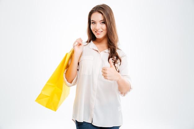 Portret szczęśliwej kobiety trzymającej torby na zakupy i pokazującej kciuk na białym tle na białej ścianie