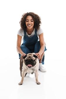 Portret szczęśliwej kobiety ubranej w dżinsowe kombinezony, kucającej i stojącej z psem mopsem na białym tle nad białą ścianą
