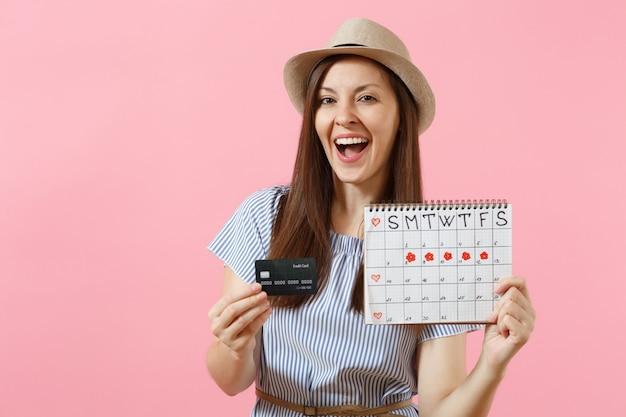 Portret szczęśliwej kobiety w niebieskiej sukience, kapeluszu trzymającym kartę kredytową, kalendarz okresów, sprawdzanie dni menstruacji na tle trendów różowy. medyczna koncepcja ginekologiczna opieki zdrowotnej. skopiuj miejsce.