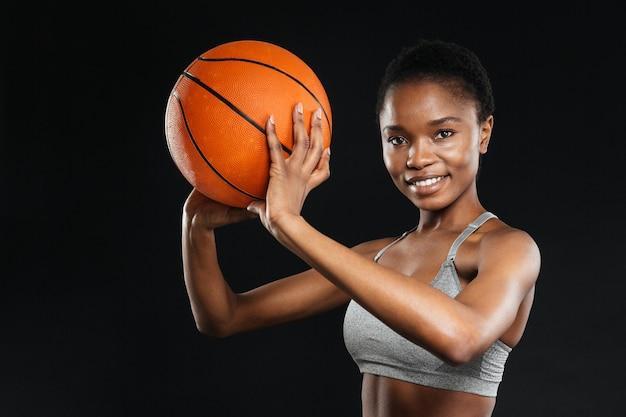 Portret szczęśliwej kobiety w odzieży sportowej trzymającej koszykówkę odizolowaną na czarnej ścianie