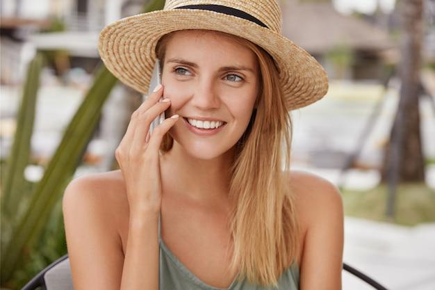 Portret szczęśliwej kobiety w słomkowym kapeluszu, ma szeroki uśmiech, pokazuje białe równe zęby, ubrana swobodnie, rozmawia przez telefon komórkowy z przyjacielem. zdjęcie pięknej młodej kobiety w kraju kurortu.