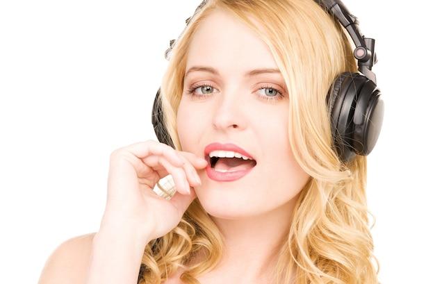 Portret szczęśliwej kobiety w słuchawkach na białej ścianie