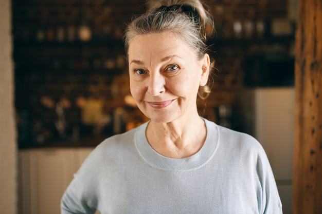 Portret szczęśliwej kobiety w średnim wieku ze zmarszczkami i niebieskimi oczami, która jest w dobrym, pozytywnym nastroju, spędzając miło czas w domu, pozując na tle przytulnej kuchni, patrząc na kamerę z wesołym uśmiechem