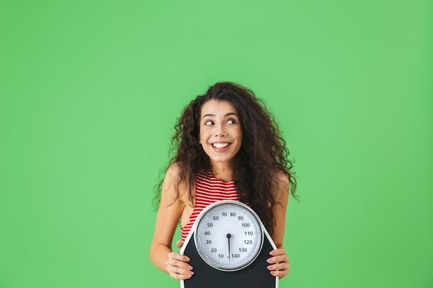 Portret szczęśliwej kobiety w wieku 20 lat w letnich ubraniach, trzymającej wagę podczas ćwiczeń na zielonej ścianie