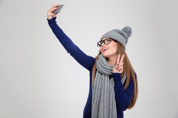 Portret szczęśliwej kobiety w zimowym materiale robi zdjęcie selfie na smartfonie i pokazuje znak pokoju na białym tle na białej ścianie