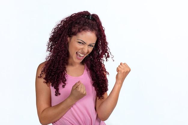 Portret szczęśliwej kobiety wibrującej z powodzeniem, zaciśniętymi pięściami
