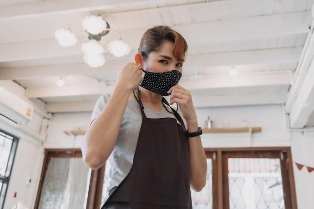 Portret szczęśliwej kobiety właściciel kawiarni i restauracji z maską na twarz