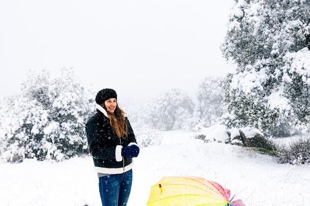 Portret szczęśliwej kobiety z kolorowym parasolem podczas opadów śniegu.