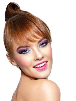 Portret szczęśliwej kobiety z kreatywną fryzurą zbliżenie twarzy pięknej kobiety z jaskrawym makijażem modelka z kreatywnym makijażem oczu na białym tle dziewczyna z rudymi włosami krótkie fryzury z grzywką