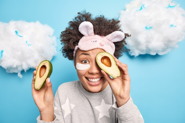 Portret szczęśliwej kobiety z kręconymi włosami zakrywa oczy połówkami awokado, lubi zabiegi pielęgnacyjne skóry, nakłada plastry pod oczy ubrane w śpiącą maskę do spania na niebieskiej ścianie