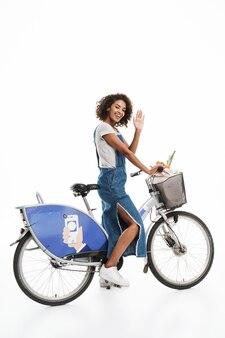 Portret szczęśliwej kobiety z torbą na zakupy macha podczas jazdy na rowerze na białym tle nad białą ścianą
