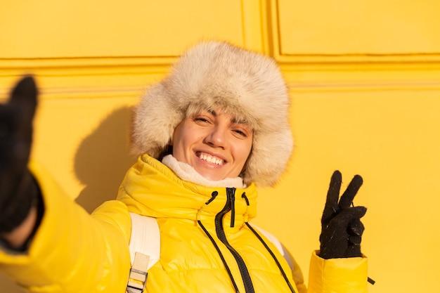 Portret szczęśliwej kobiety z uśmiechem w śnieżnobiałych zabach zimą na żółtej ścianie w słoneczny dzień w ciepłym rosyjskim syberyjskim kapeluszu